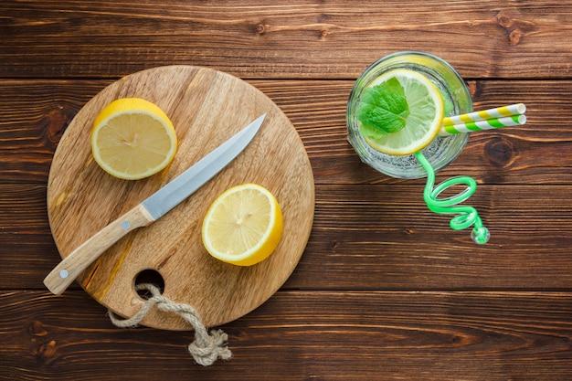 Set snijplank, stro, witte doek, houten mes en gesneden citroen in een kom op een houten oppervlak. bovenaanzicht.