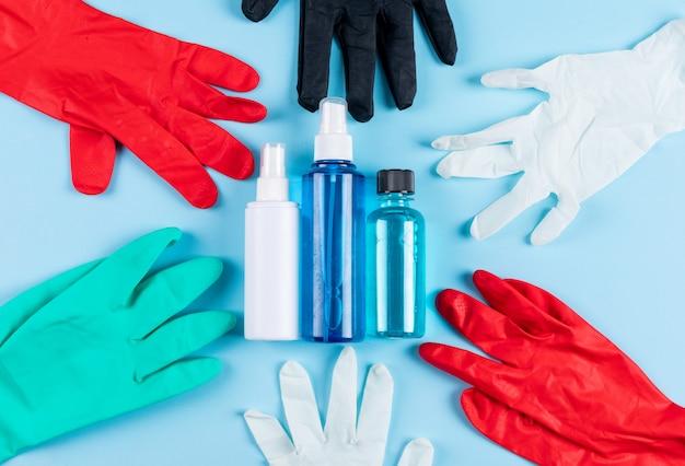 Set sprays, medisch masker en medische handschoenen op een licht cyaan achtergrond. bovenaanzicht.