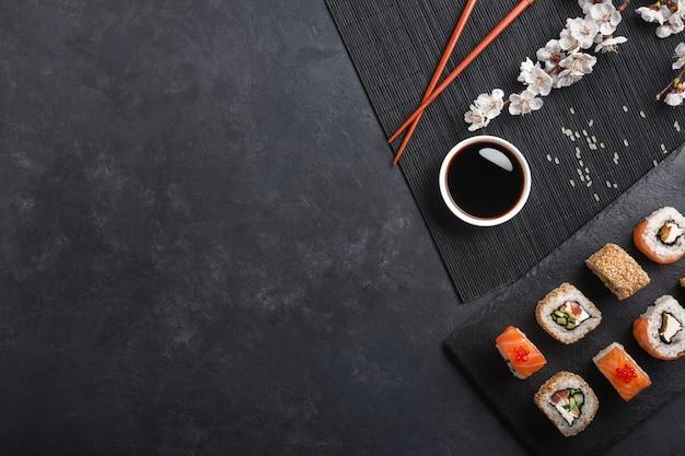 Set sushi en maki broodjes met tak van witte bloemen op stenen tafel. bovenaanzicht.