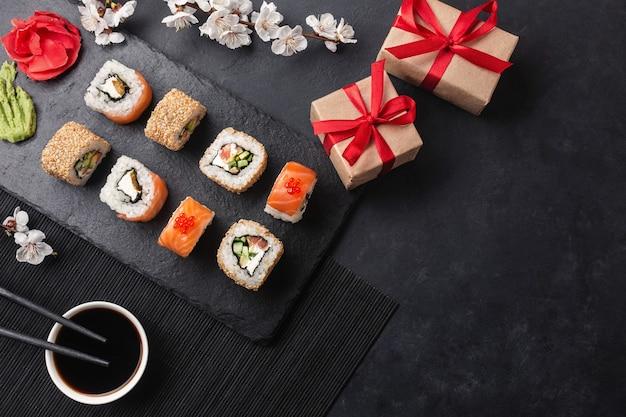Set sushi, maki broodjes, geschenkdozen met tak van witte bloemen op stenen tafel bovenaanzicht.