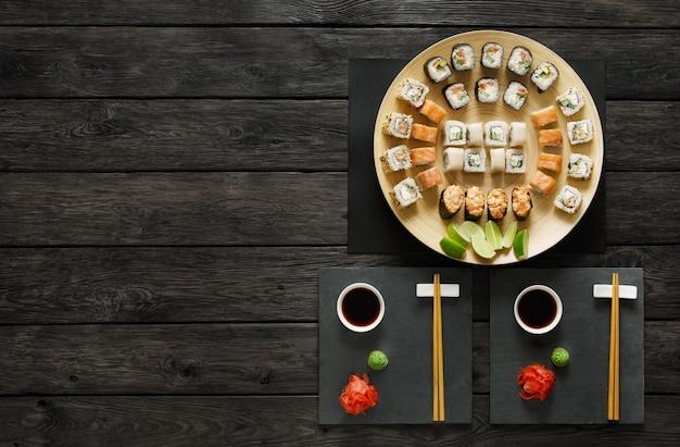 Set sushi maki en broodjes op zwart rustiek hout