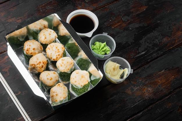 Set sushi rolt in de doos van de leveringvoedsel, op oude donkere houten tafel