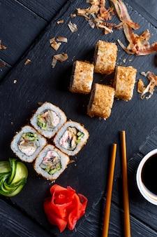 Set sushi rolt met roomkaas, rijst en krab op een zwart bord versierd met gember en wassabi op een donkere houten tafel. japanse keuken. eten fototafel
