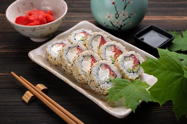 Set sushibroodjes met roomkaasrijst en zalm op een bord versierd met gember op een hout