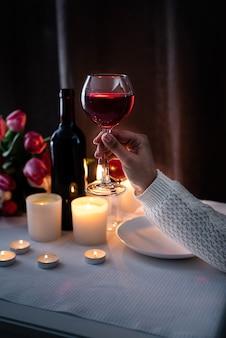 Set tafelgerei met boeket tulpen, wijn en kaarsen, donkere achtergrond. vrouw hand met een glas wijn
