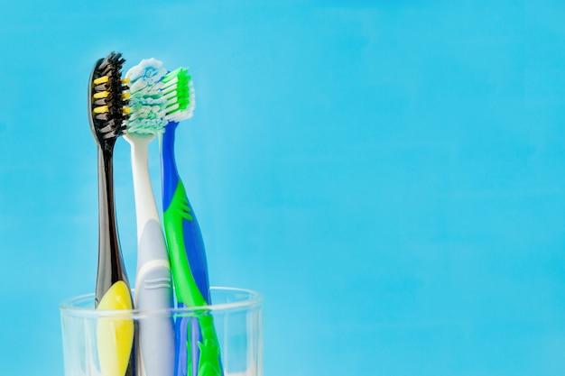 Set tandenborstels in glas op blauwe muur. concept tandenborstel selectie, kopie ruimte