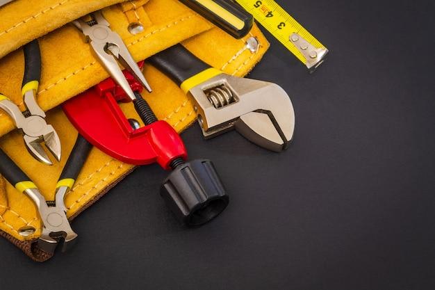 Set tools in suède tas op zwarte achtergrond