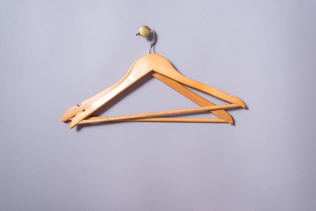 Set van 2 lege houten gelakte kleerhanger hangen grijze muur achtergrond