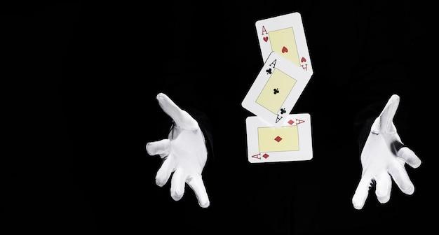 Set van azen speelkaart in de lucht tussen de handen van de goochelaar