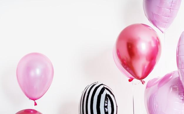 Set van ballonnen in de vorm van een hart en ronde roze en gestreept op lichte achtergrond met kopie ruimte.