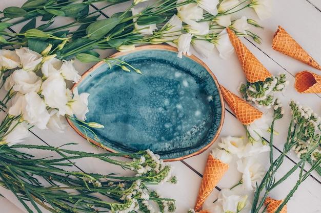 Set van bloemen en ijs kegels en blauw bord op wit hout. bovenaanzicht.