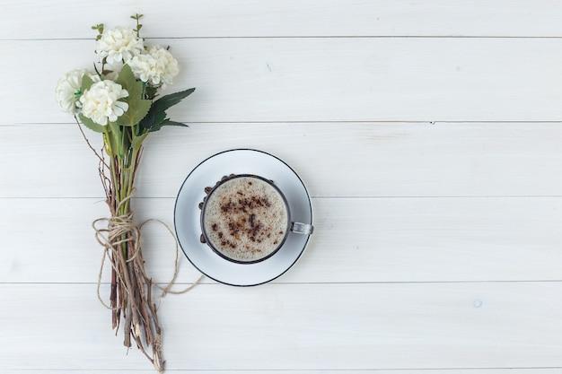 Set van bloemen en koffie in een kopje op een houten achtergrond. bovenaanzicht.