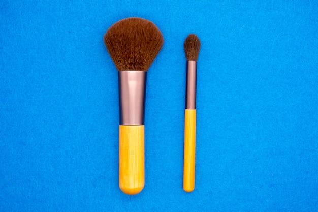 Set van borstels voor make-up chaotisch verspreid op blauwe achtergrond