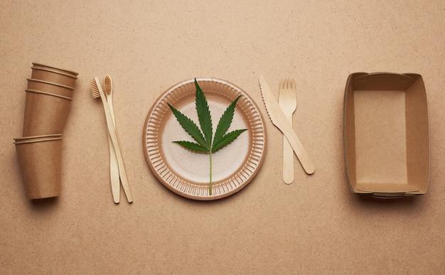 Set van bruine papieren borden, bekers en houten vorken en messen op een bruine achtergrond, plat lag.