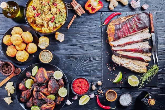 Set van caribische gerechten, gemarineerde varkensbuik, kipcurry, gefrituurde dumplings, geroosterde kippendijen en drumsticks op borden op een zwarte houten tafel, uitzicht van bovenaf, flatlay