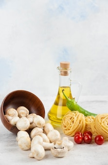 Set van champignons, extra vergine olijfolie, pasta's, cherrytomaatjes en chilipepers op een stuk marmer.