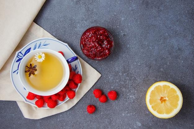 Set van citroen, frambozen en frambozenjam in schoteltjes, en een kopje kamille thee op een doek