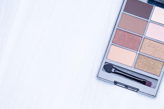Set van cosmetica schaduwen voor make-up. maak naakt essentials op witte houten achtergrond. plat lag, kopie ruimte, bloggen concept.
