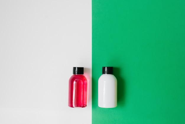 Set van cosmetische producten voor douche of bad, witte en roze flessen op witte en groene achtergrond. kopieer ruimte
