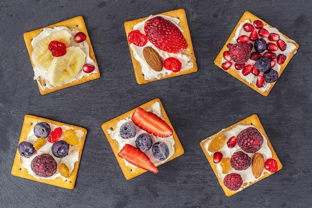 Set van crackers met verschillende soorten fruit op een donkere leisteenplaat. bovenaanzicht.