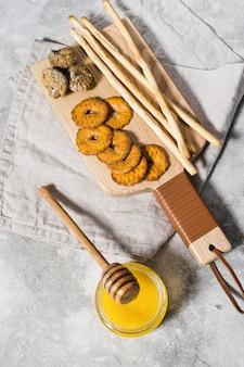 Set van crackers op houten snijplank, honing.