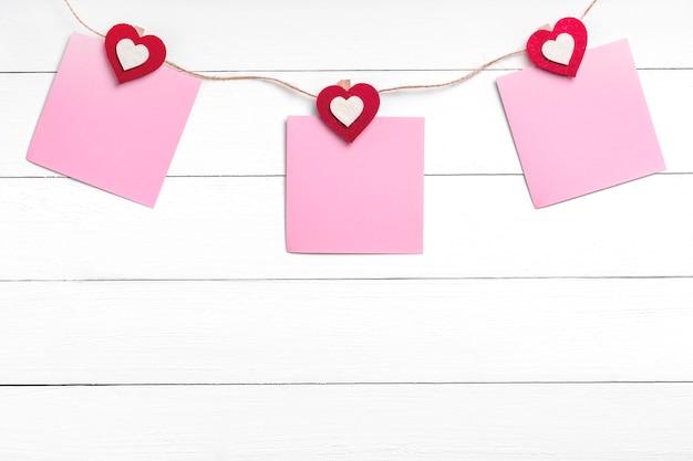 Set van drie lege stickers opknoping op string met wasknijpers achter witte houten oppervlak. aantekeningen op papier gehouden op touw met rode harten. kopieer ruimte, bovenaanzicht.