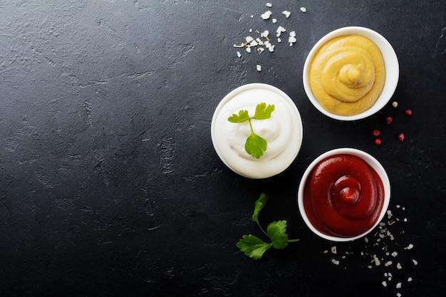 Set van drie sauzen - mayonaise, mosterd en ketchup in witte keramische kommen op zwarte steen of beton.