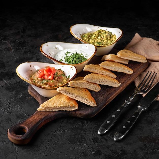 Set van drie soorten dipsauzen: tzatziki, guacamole, auberginekaviaar op rustieke houten plank.