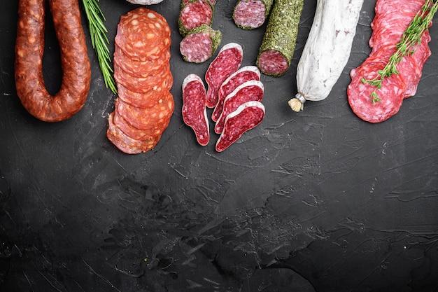 Set van droge genezen salami, spaanse worst, plakjes en bezuinigingen op zwart, bovenaanzicht met kopie ruimte