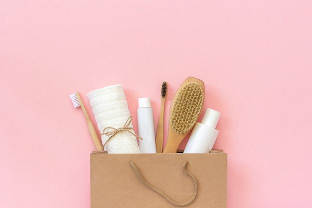 Set van eco cosmetica producten en hulpmiddelen voor douche of bad in papieren zak op roze achtergrond.