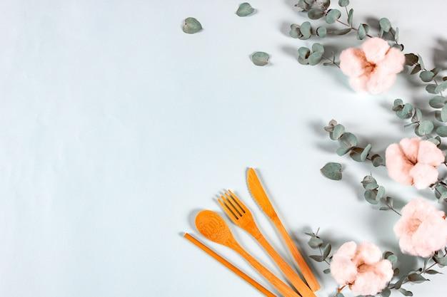 Set van eco natuurlijke houten lepel, vork, mes rietjes om te drinken, eucalyptus bladeren en katoen bloemen