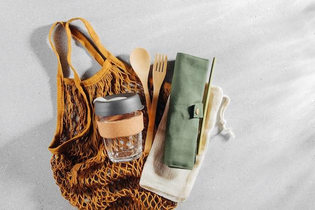 Set van eco vriendelijk bamboe bestek, eco tas en herbruikbare koffiemok. duurzame levensstijl. kunststofvrij concept.