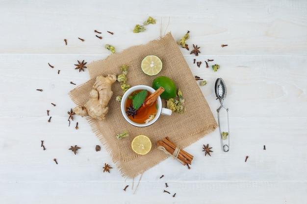 Set van een theezeefje en een kopje thee, limoenen, gember en kaneel in een linnen placemat op een grijze ondergrond
