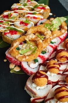 Set van gebakken sushibroodjes ligt op bamboebladeren geserveerd op zwarte stenen leisteen.