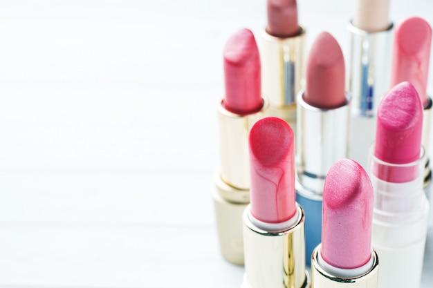 Set van gekleurde roze lippenstift op witte achtergrond. cosmetica voor vrouwen. selectieve aandacht. ruimte kopiëren.
