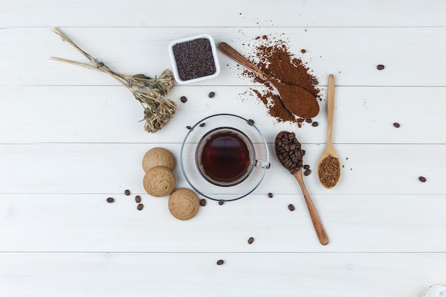 Set van gemalen koffie, koffiebonen, gedroogde kruiden, koekjes en koffie in een kopje op een houten achtergrond. bovenaanzicht.