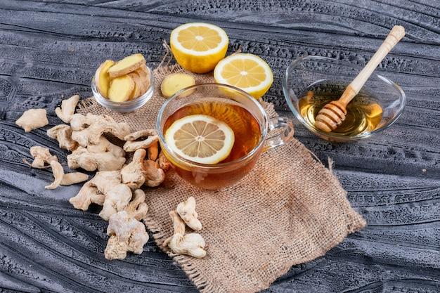 Set van gember, citroen en honing en een thee op zak doek en donkere houten achtergrond. hoge hoekmening.