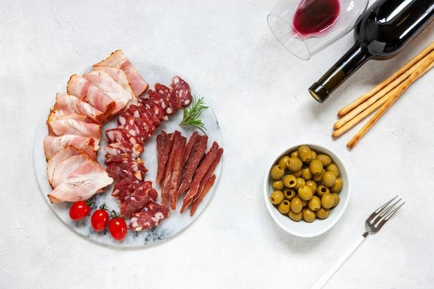 Set van gerookt spek, salami en basturma geserveerd met gepekelde olijven, tomaten, wijn en grissini brood