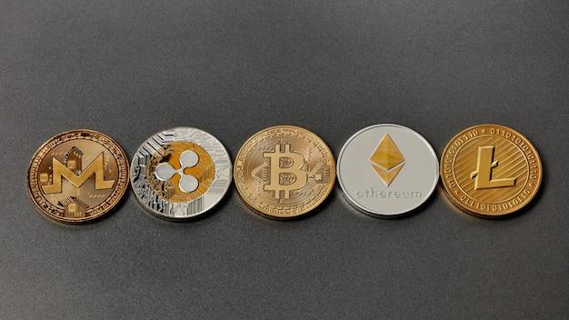 Set van gouden en zilveren munten monero, rimpel, bitcoin, litecoin, ethereum, streepje op een zwarte achtergrond. conceptueel beeld voor wereldwijde cryptocurrency en digitaal betalingssysteem. bovenaanzicht
