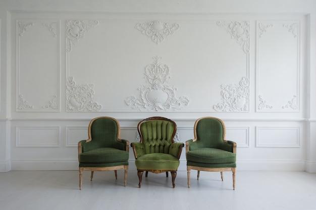 Set van groene houten vintage stoelen staan voor een witte muur