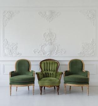 Set van groene houten vintage stoelen voor een witte muur ontwerp bas-reliëf stucwerk lijstwerk roccoco elementen op lichte parketvloer.
