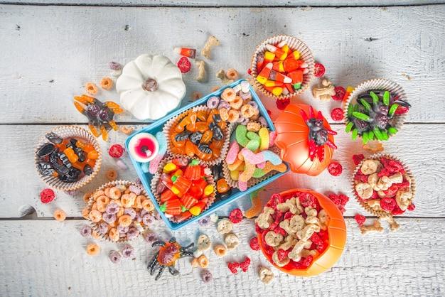 Set van halloween snoep en snoep. verschillende kindertraktaties voor halloween - snoep, ontbijtgranen, snoep, met schoollunchbox en emmer, flatlay kopieerruimte bovenaanzicht
