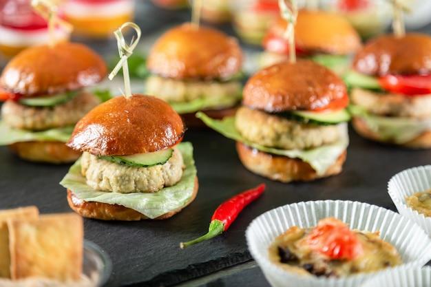 Set van hamburgers op zwarte bord op houten tafel