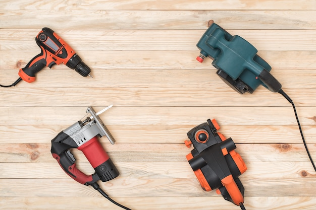 Set van hand timmerwerk elektrische gereedschappen voor houtbewerking ligt op een lichte houten achtergrond.