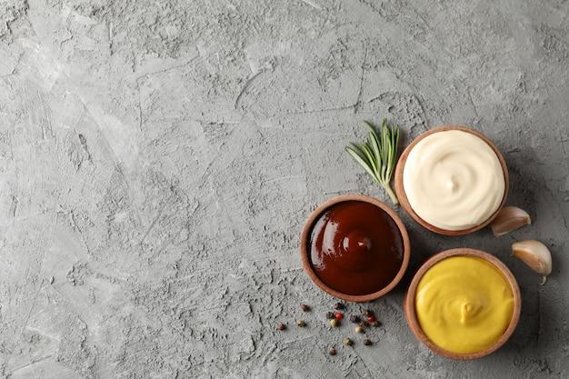 Set van heerlijke smakelijke saus, ingrediënten op grijze achtergrond, ruimte voor tekst. bovenaanzicht