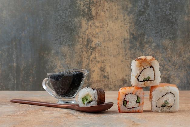 Set van heerlijke sushi roll met lepel en sojasaus op marmeren oppervlak