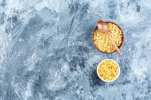 Set van houten lepel en rauwe pasta in kommen op een grijze gips achtergrond. bovenaanzicht.