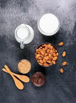 Set van houten lepel, hazelnootpasta met cacao, melk en amandelen in een kom op een zwarte stenen tafel. hoge hoekmening.