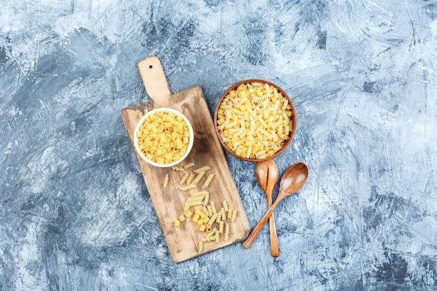 Set van houten lepels en diverse pasta in kommen op een grijze achtergrond van gips en snijplank. bovenaanzicht.