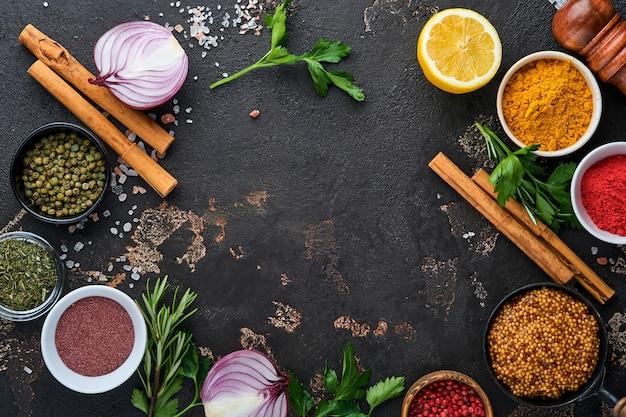 Set van indiase geurige specerijen en kruiden op een zwarte stenen achtergrond. kurkuma, dille, paprika, kaneel, saffraan, basilicum en rozemarijn in een lepel. bovenaanzicht. bespotten.